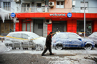 Pictured: A man walks past cars covered in thick ice in central Salonika, Greece. Monday 09 January 2017<br />
