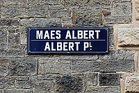 Pictured: Albert Place (Maes ALbert) road sign on the old Police Station in Aberystwyth, Wales, UK. Wednesday 28 August 2019<br /> Re: Opened 1866, built by the Hafod Hotel Co as the Queens Hotel; architects, Hayward and Davies; builder George Lumley of Aberystwyth. Sold in 1877 and later converted to local government use; remodelled in1950 by G R Bruce, County Architect.<br /> Detached towards N end of the Promenade, with main entrance to side elevation in Albert Place and rear elevation to Queens Road.<br /> Hotel de Ville style. Asymmetrical 3-storey attic and basement snecked rubble 13-bay W (Promenade) elevation; stepped front with mostly vermiculated dressings, stock brick voussoirs, deep entablature and cornice and cill bands; buttresses to ground floor centre. Steep pitch mansard slate roof with truncated chimney stacks. Dormers with steep overhanging roofs and casement windows; paired to left. 3-bays advanced near the right hand end and with additional storey and splayed angles to 2nd floor (with small cast-iron parapets) and 3rd floor; also to top floor) with small cast-iron parapets) and 3rd floor; also to top floor at the corner. Sash windows, some paired; anthemion panelled cast-iron window box holder across central bays.