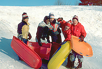 Friends age 11 snow sledding. St Paul Minnesota USA