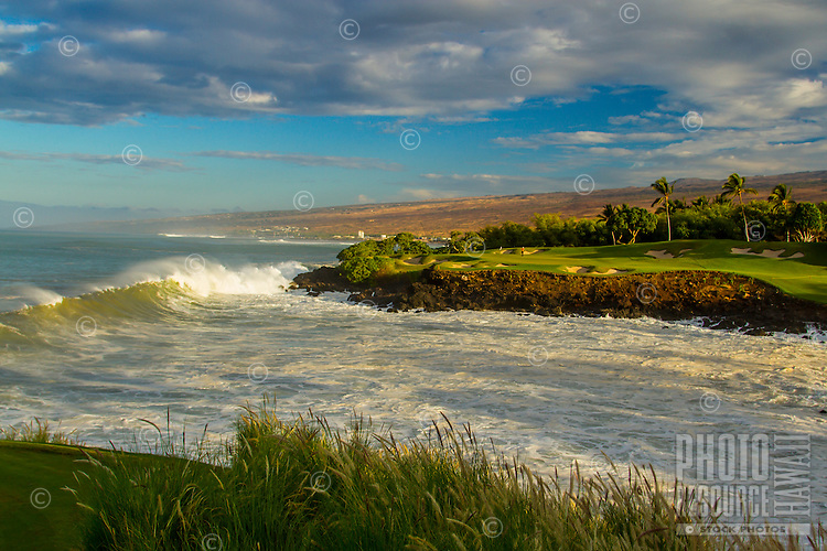 As the sun rises, a wave breaks near Hole No. 3 of Mauna Kea Golf Course and through Kauna'oa Bay, Big Island.