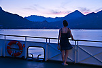 Woman on a ferry boat, looks at the sunset over the town of Menaggio on Lake Como, Italy