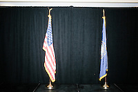 An American flag and New Hampshire flag stand on the stage after Republican presidential candidate and real estate mogul Donald Trump left a meeting of the New England Police Benevolent Association executive council at the Sheraton Portsmouth Harborside Hotel in Portsmouth, New Hampshire, USA. Earlier in the evening, the group endorsed Trump for president. A small group of perhaps 20 Trump supporters stood outside the hotel and there was a larger group of anti-Trump protesters, mostly across the street. One of the protest organizers estimated that there were around 230 protesters gathered.Many protesters expressed disagreement with Trump's recent statements that he would ban all Muslims from entering the country. Trump brought up the recent shooting in San Berdardino, Calif., at the meeting.