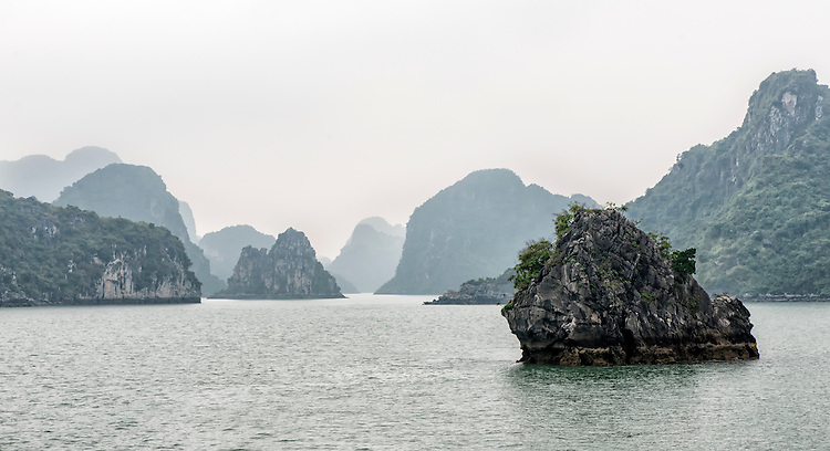 """Ha Long Bay, located on the east coast of Vietnam near Haiphong, contains over 1,900 limestone """"karst"""" islands projecting from the sea. They are frequently shrouded in fog, mist and rain, as seen in these photos."""