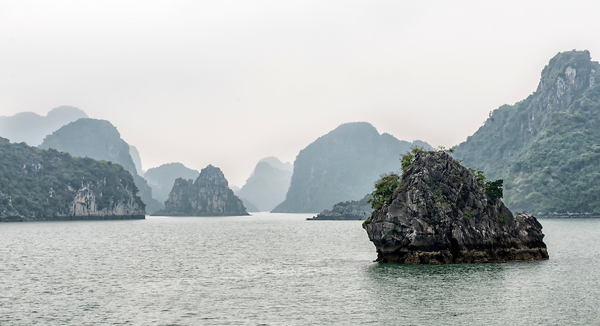 "Ha Long Bay, located on the east coast of Vietnam near Haiphong, contains over 1,900 limestone ""karst"" islands projecting from the sea. They are frequently shrouded in fog, mist and rain, as seen in these photos."