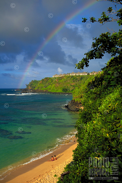 A couple admires a rainbow at golden Hideaways Beach, Princeville, Kauai
