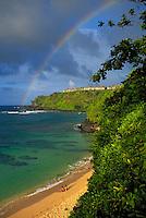 A couple admires a rainbow at golden Hideaways Beach, Princeville, Kauai