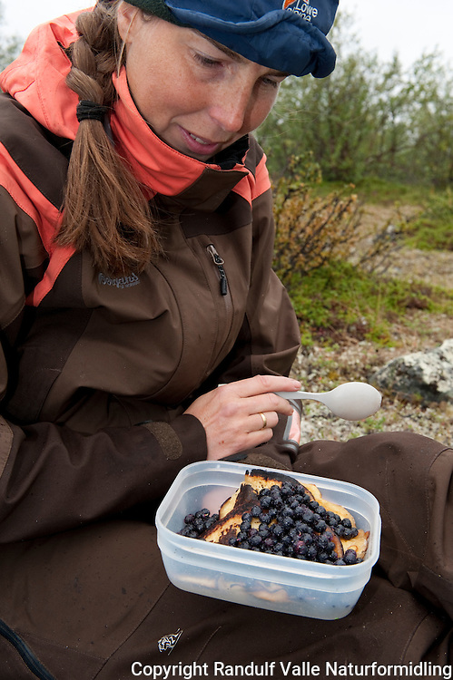 Dame spiser pannekaker med blåbær. ---- Woman eating pan cakes with blueberries.
