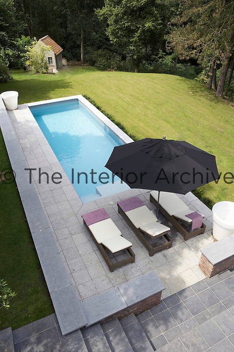 The elegant swimming pool is situated on a stone-paved terrace adjacent to the lawn