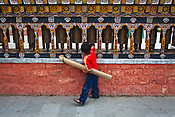 A young Bhutanese boy is seen turning the prayer wheels at the clock tower, the main square in Thimphu, Bhutan. Photo: Sanjit Das/Panos