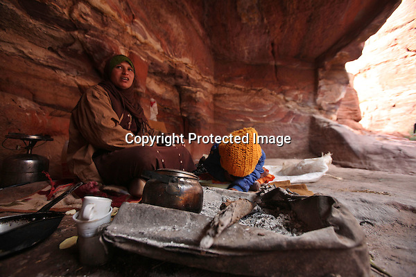 Bdoul bedouin Um Mohammed and her daughter Yasmine who hides her head down from the camera with a yellow hat, sit in their cave in Petra, Jordan. (Salah Malkawi for The National)