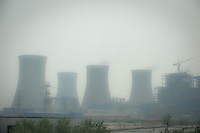 Daytime landscape view from the Tianjin Binhai Light Rail of cooling towers at an industrial site near the Binhai New Area Tanggu District in Tiānjīn.  © LAN