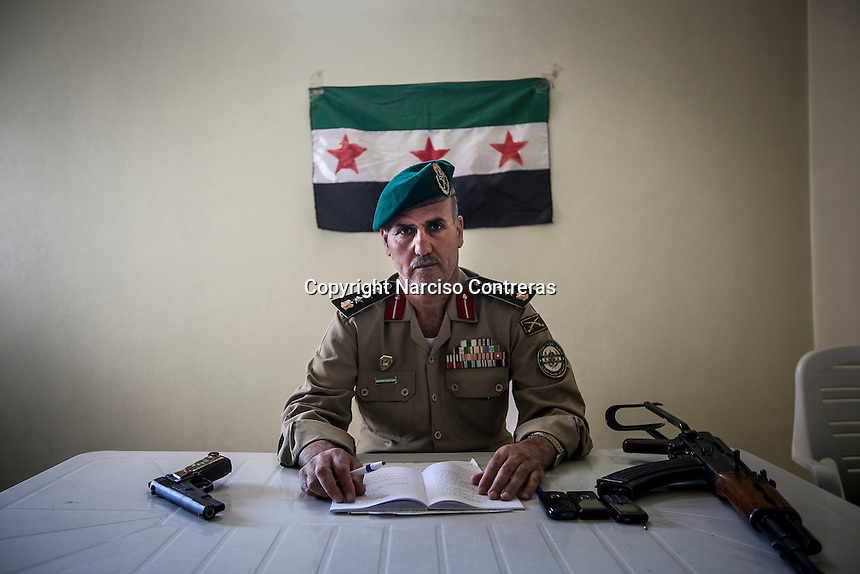 GENERAL ABNASER FARASAT a former Syrian army member, sits at his headquarters in Anadan village, one of the ghost towns in northern of Aleppo province.