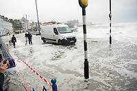 Pictured: A van and a tv crew are caught up in water caused by waves that crash against the seaside town of Aberystwyth, Wales, UK. Saturday 21 October 2017<br /> Re: Coastal parts of the UK is facing winds of up to 70mph as Storm Brian causes roads to close and public transport to be cancelled.<br /> Roads in Aberystwyth's seafront and at nearby Aberaeron, Wales are shut on Saturday morning as a yellow &quot;be aware&quot; Met Office warning is in place.<br /> Seven flood warnings have been issued for the west Wales coast.