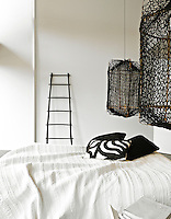 The bedroom is minimally furnished and the low-slung bed is flanked by a pair of netting pendant lights
