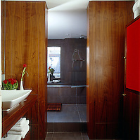 A distinctly masculine bathroom with wood panelled walls and a sunken ceramic and stone bath
