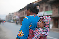 A woman carries her baby on her back in a street of Bhaktapur, outside of Kathmandu, Nepal. May 05, 2015