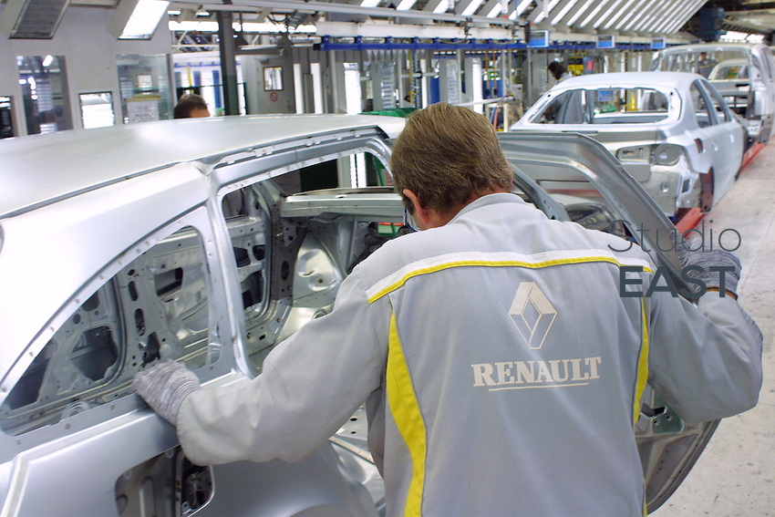 Worker Auguste Gallais checks the body of a Renault Laguna car before the painting process, in Renault plant, in Sandouville, France, on September 18, 2002. Photo by Lucas Schifres/Pictobank