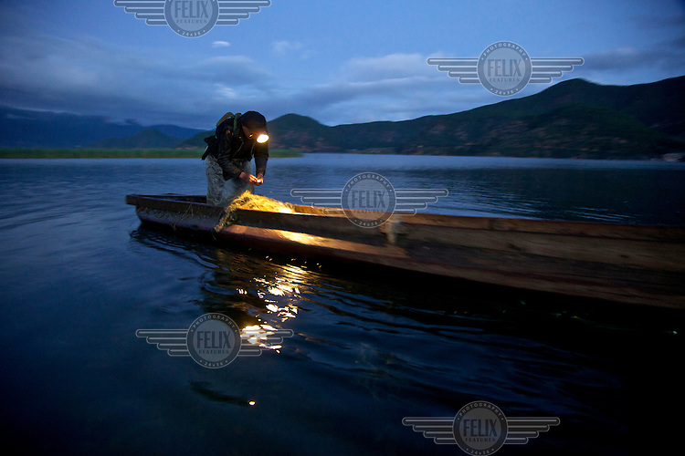 A fisherman checks his nets by torch light as night falls on Lugu Hu Lake. /Felix Features