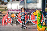 A boy in a blue shirt walks towards an animal spraying water at him with an open mouth, in front of the iconic train in the splash pad at Stanton Central Park.