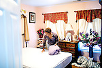 Karen Morris has been caring for her mother Gloria, 80, for the past 10 years. Her mother has Alzheimer's disease and lives with Karen and Karen's husband Richard in their Charlotte, NC home. She clears the bed before bathing her mother...Mrs. Morris was a nurse before she retired and really enjoys taking care of people, she said. Every morning she washes her mother in the bathroom, helps her walk down the stairs, and they share breakfast, as they did Monday, October 18, 2010...Gloria was having an especially bad day and because Karen sees her every day, she knew something was wrong. She later discovered her medication was dehydrating her. That is one of many reasons why having a regular caretaker is so important. ..Kendrick Brinson.LUCEO.Model Released: Yes.AARP Contract #4859.Wichita/Bellovin Bulletin..