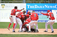 Batavia Muckdogs outfielder Victor Castro (40) is mobbed by teammates including Mason Davis (7), Alexander Carreras (43), Carlos Duran (30), Luis Alberto Sanz (19), Miles Williams (26), Kevin Grove (12), Ryan Aper (3) and Wildert Pujols (38) after a walk off single during a game against the Lowell Spinners on July 17, 2014 at Dwyer Stadium in Batavia, New York.  Batavia defeated Lowell 4-3.  (Mike Janes/Four Seam Images)