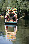 Mexico City. Xochimilco; relaxing on the river in one of the brightly coloured punts which make the area famous.