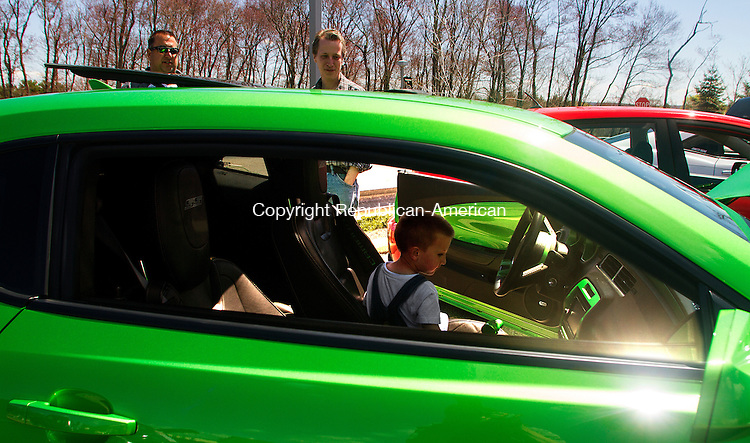 PLYMOUTH, CT - 02 APRIL 2015 - 050215JW01.jpg -- Mason Gomme age 5 gets a chance to sit in the drivers seat of the 2011 Chevy Camaro owned by Chet Kaniecki of Groton as his father Ted Gomme and Kaniecki look on during the 6th Annual Plymouth Car Show Saturday afternoon. Jonathan Wilcox Republican-American