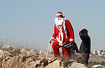 A Palestinian man, wearing a Santa Claus costume looks on during clashes with Israeli soldiers in the West Bank village of Bilin, west of Ramallah, following a march organized in solidarity with the people of the village against the construction of settlements and the confiscation of their land on December 26, 2014. Photo by Shadi Hatem