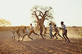 Dodoma, Tanzania. Teenagers playing football in the dust of the late afternoon sun.