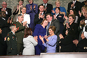Janet Norwood, in blue at center of the photo and her husband, William Norwood of Pflugerville, Texas, hug as they are recognized during the State of the Union Address delivered by United States President George W. Bush in Washington, D.C. on February 2, 2004.  They are the parents of twenty-five year-old Sergeant Byron Norwood, a member of the 3rd Battalion 1st Marine Regiment Combined Anti-Armor Team.  He was killed in combat on November 13, 2004, by sniper fire during the assault on the city of Fallujah.  Sergeant Norwood was decorated with the Purple Heart and the Combat Action Ribbon.  Mrs. Norwood wrote a letter to the President in December 2004 expressing her support of his efforts in Iraq.  <br /> Credit: Luke Frazza / Pool via CNP