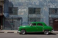 green oldtimer in front of blue wall in Havana, Cuba