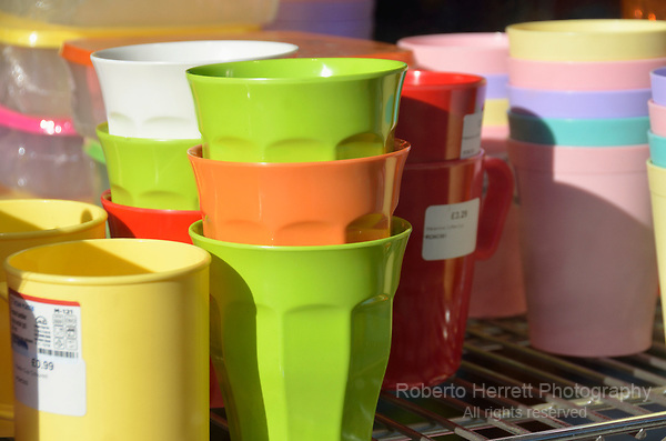 Coloured plastic cups in a shop window display.
