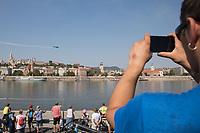 Man takes a photo with his mobile phone of an aerobatic plane perform during an Air show above River Danube that celebrates Hungarian national holiday on the anniversary of state foundation in Budapest, Hungary  on Aug. 20, 2018. ATTILA VOLGYI