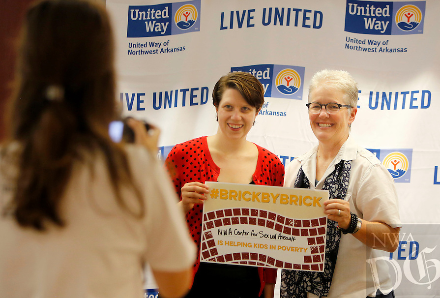 NWA Democrat-Gazette/DAVID GOTTSCHALK  Kristen Jenson (from left), an intern with the United Way of Northwest Arkansas, photographs Chelsea Miller and Anne Shelley, with the Northwest Arkansas Center for Sexual Assault,  Thursday, August 27, 2015 at the beginning of the annual United Way of Northwest Arkansas annual campaign kickoff at the Donald W. Reynolds Center for Enterprise Development on the campus of the University of Arkansas in Fayetteville. This year the workplace campaign will focus on educating the community about a pathway out of poverty for childrent and how to get involved to help change the statistics. Keynote speaker for the morning event was congressman Steve Womack.