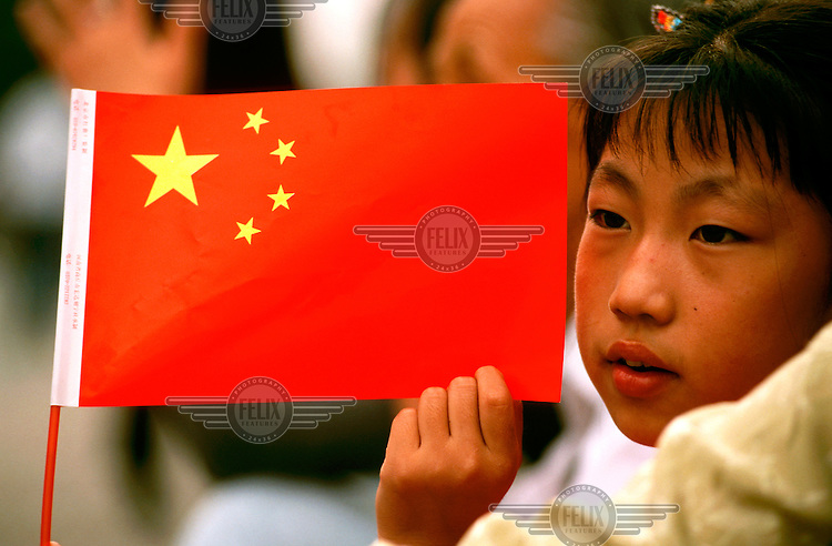 Mark Henley/Panos Pictures..China, Beijing..Patriotic girl holding the flag of the PRC.