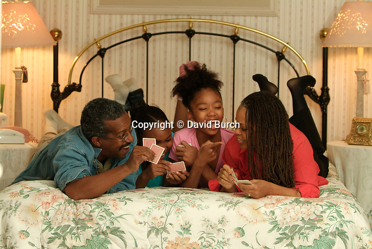 African American couple playing cards with  their grand children