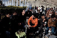 Young men smoke shisha (water pipes) in Shar Park in front of the Citadel in Erbil.