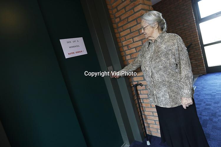 Foto: VidiPhoto<br /> <br /> KESTEREN &ndash; Een tiental bejaarden van Schenkhof in Kesteren, gemeente Neder-Betuwe, zit donderdag al acht dagen opgesloten in hun woningen. Dat is niet de eerste keer. Enkele weken geleden moesten ze al tien dagen in hun kamers blijven. Oorzaak is een kapotte lift die zich moeilijk laat repareren. De achttien aanleunwoningen van Schenkhof zijn verbonden aan het reformatorische verzorgingshuis &rsquo;t Anker. De bejaarden wonen zelfstandig, maar zijn slecht ter been. Op de bovenste twee verdiepingen kunnen nog slechts twee bewoners min of meer zelfstandig gebruik maken van de trap. De andere tien bovenbewoners zijn aangewezen op de lift die niet meer werkt. De bewoners reageren boos, maar ook emotioneel op hun gedwongen gevangenschap in de &ldquo;gouden kooi&rdquo; zoals ze het zelf omschrijven. Boodschappen doen of koffiedrinken beneden in het verzorgingshuis is er niet meer bij. Ook in geval van brand of een andere calamiteit kunnen de mensen niet weg. Vrijwilligers en familieleden moeten nu bijspringen om de boodschappen te doen en waar nodig voor eten te zorgen.