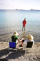 Three people wearing straw hats sitting on beach<br />