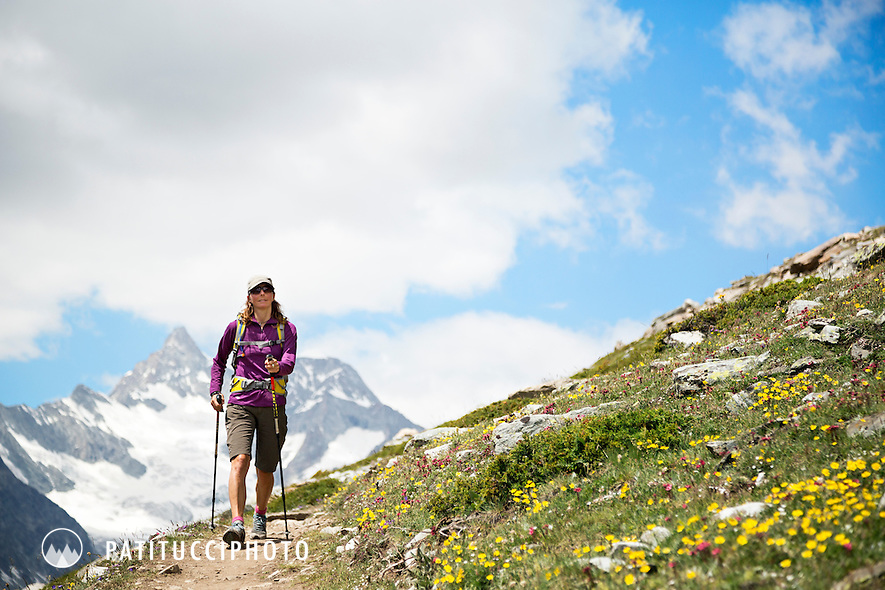 A woman hiking in the dramatic landscape high above Zermatt, Switzerland with the Obergabelhorn in the background