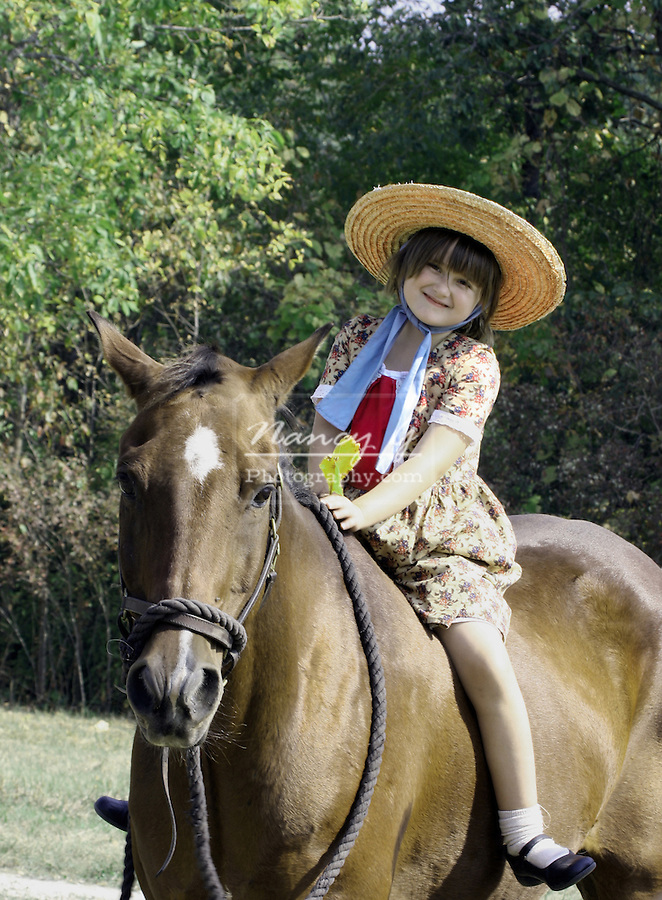 A young girl riding bareback on a horse at a civl war reenactment