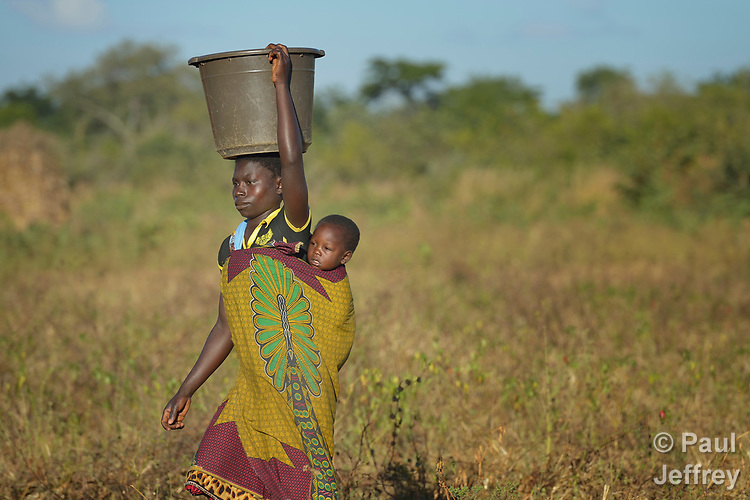 Child on her back, a woman carries water from a community well to her home in Chibamu Jere, Malawi. Women in the village get support from the Maternal, Newborn and Child Health program of the Livingstonia Synod of the Church of Central Africa Presbyterian.