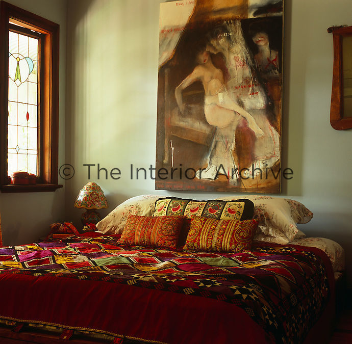 The bedroom is decorated in Miv's signature combination of ethnic, coloured and patterned fabrics with a painting by a local artist on the wall