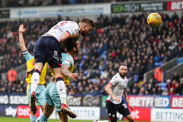 Bolton Wanderers' Mark Beevers heads at goal under pressure from Rotherham United's Joe Mattock<br /> <br /> Photographer Andrew Kearns/CameraSport<br /> <br /> The EFL Sky Bet Championship - Bolton Wanderers v Rotherham United - Wednesday 26th December 2018 - University of Bolton Stadium - Bolton<br /> <br /> World Copyright © 2018 CameraSport. All rights reserved. 43 Linden Ave. Countesthorpe. Leicester. England. LE8 5PG - Tel: +44 (0) 116 277 4147 - admin@camerasport.com - www.camerasport.com