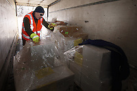 "February 16, 2013  Volunteer  Chris Burns unloads musher's food bags from a van at the Willow airport on the first day of the ""Food Fly"", where Iditarod air force pilots fly supplies to the 4 checkpoints on the east side of the Alaska Range. ..Iditarod 2013  Photo Copyright Jeff Schultz  -- Do not reproduce without written permission"