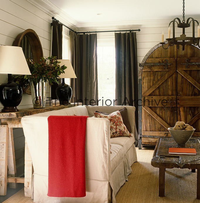 A comfortable and inviting family room has a pair of antique French doors made into a media cabinet
