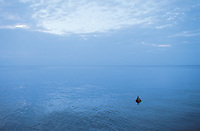 A man lies in an inner tube floating alone in the sea infront of Havana, Cuba 9-02