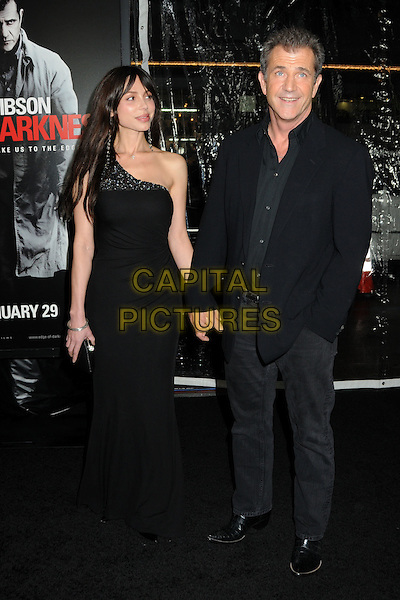"OKSANA GRIGORIEVA & MEL GIBSON.Attending the ""Edge of Darkness"" Los Angeles Premiere held at Grauman's Chinese Theatre, Hollywood, California, USA, 26th January 2010..arrivals full length long maxi dress suit jacket hand in pocket holding hands clutch bag black shirt one shoulder  couple beaded jewel encrusted embellished  .CAP/ADM/BP.©Byron Purvis/AdMedia/Capital Pictures."