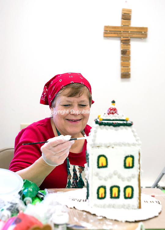Middlebury, CT- 04 December 2015-1204115CM06-  Karen Stowell, a parishioner at St. George's Episcopal Church decorates a gingerbread house at the church on Friday.  Volunteers spent the day making final preparations for its annual Gingerbread House Village, which opens Saturday from 10 a.m. until 7p.m.  For specific dates and times, log onto the web and go to: http://www.gingerbreadvillagect.com.     Christopher Massa Republican-American