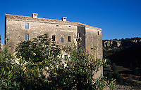 A view over the olive trees to the side elevation of the 12th century chateau de Balazuc